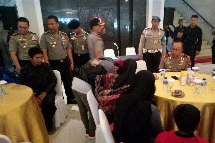 Irawan Maulana (22) Korban selamat dalam peristiwa penyerangan oleh kelompok KKB terhadap pekerja di Nduga Papua, tiba di Mapolda Jabar, Kota Bandung, Jawa Barat, Selasa (11/12/2018) sekira pukul 08.00 WIB. Irawan yerlihat langsung mencium tangan orang tuanya.