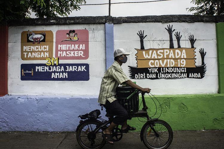 Warga melintas di depan mural yang berisi pesan waspada penyebaran virus Corona di Petamburan, Jakarta, Rabu (16/9/2020). Mural tersebut dibuat untuk mengingatkan masyarakat agar menerapkan protokol kesehatan saat beraktivitas karena masih tingginya angka kasus COVID-19 secara nasional. ANTARA FOTO/Aprillio Akbar/aww.