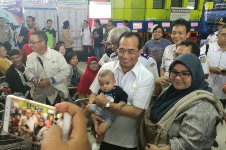 Menteri Perhubungan Budi Karya Sumadi menggendong bayi dari calon penumpang kereta api di Stasiun Gambir, Jakarta, Jumat (14/4/2017)