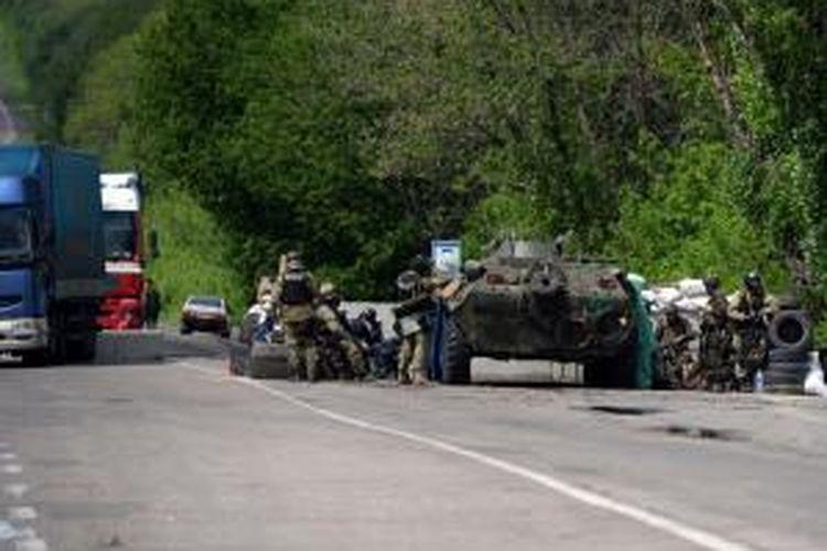 Pasukan Ukraina diperkuat sebuah kendaraan lapis baja bersiaga di sebuah pos pertahanan di dekat kota Slavyansk yang dikuasai kelompok separatis. Dalam baku tembak, Senin (5/5/2014), sebanyak empat prajurit Ukraina tewas dan satu helikopter serbu Mi-24 jatuh.