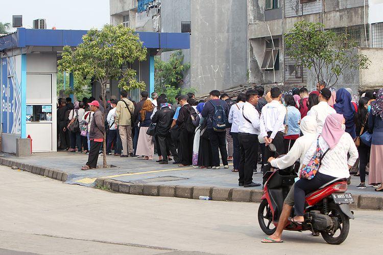 Ratusan orang calon penumpang mengantre untuk menaiki bus Trans Jakarta di Halte Puri Beta 2, Larangan, Tangerang, Banten, Senin (16/3/2020). Antrean panjang tersebut terjadi akibat adanya pengurangan jam operasional bus serta jumlah bus yang beroperasi yang tujuannya untuk pencegahan penularan COVID-19.