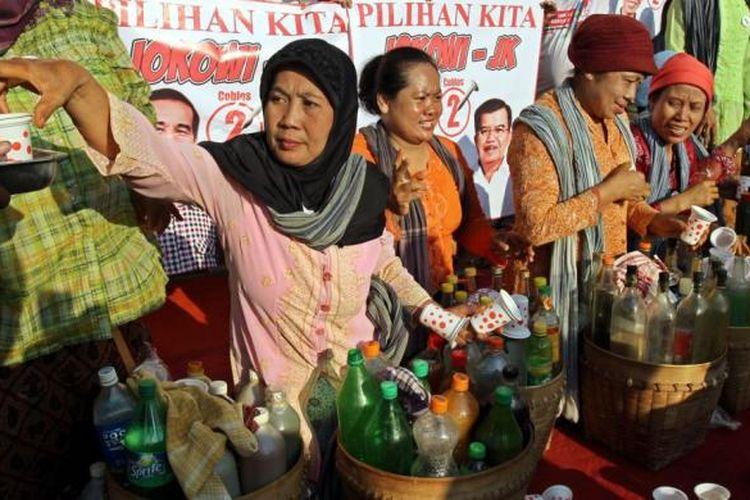 Penjual jamu gendong memberikan jamu gratis kepada warga yang sedang menikmati car free day di sekitar bundaran HI Jakarta Pusat, Minggu (8/6/2014). Penjual jamu ini memberikan jamu gratis sebagai ungkapan dukungannya kepada pasangan Jokowi-JK.