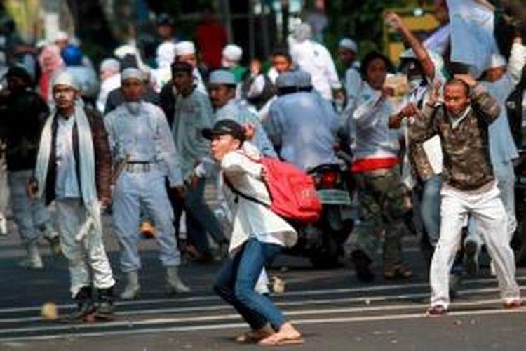 Massa Front Pembela Islam (FPI) melemparkan batu ke arah Gedung DPRD DKI Jakarta saat melakukan aksi unjuk rasa, Jumat (3/10/2014). Massa FPI berdemo menolak Ahok diangkat menjadi Gubernur DKI Jakarta.