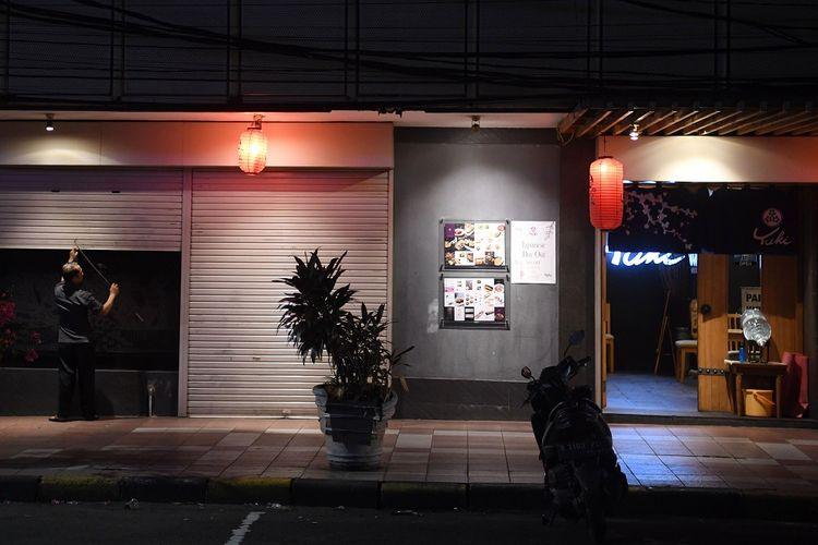 Seorang pekerja menutup restoran saat pemberlakuan PPKM di kawasan Blok M Jakarta, Rabu (21/7/2021). Pemerintah mengeluarkan dua aturan terkait perpanjangan PPKM, diantaranya penutupan pusat perbelanjaan dan pelarangan makan ditempat bagi restoran di wilayah Jawa-Bali yang masuk PPKM level 4 dan pembukaan opersiaonal pusat perbelanjaan hingga pukul 17.00 WIB dan pembatasan pengunjung sebesar 25 persen saat PPKM level 3 di 28 kabupaten/kota. ANTARAFOTO/Wahyu Putro A/foc.