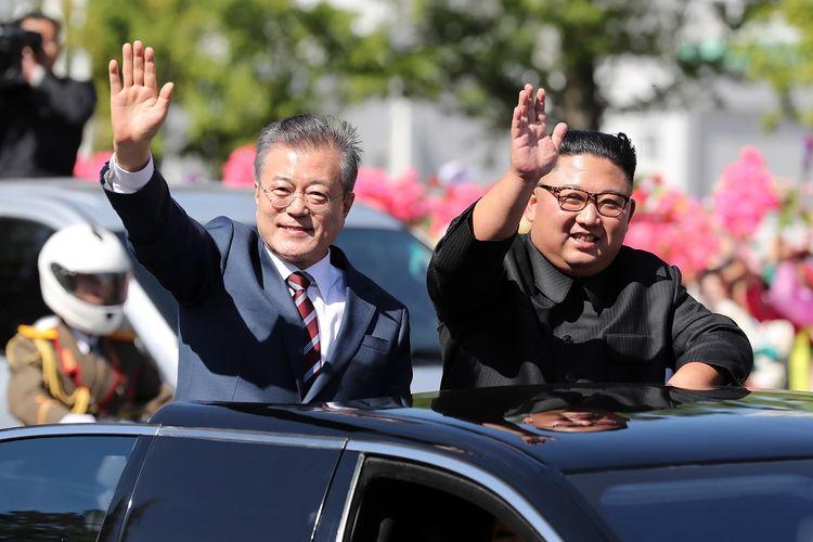 Pemimpin Korea Utara Kim Jong Un (kanan) dan Presiden Korea Selatan Moon jae-in melambaikan tangan menyapa warga di Pyongyang Selasa (18/9/2018). Moon memulai kunjungan selama tiga hari dengan denuklirisasi menjadi agenda utama.