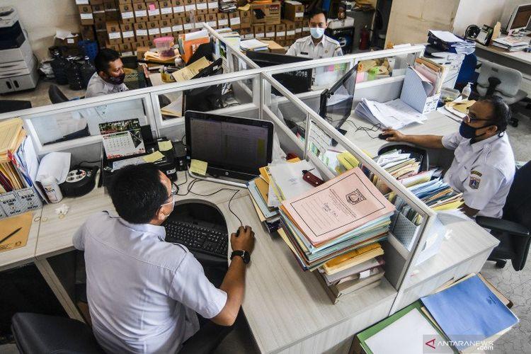 Pegawai Badan Kepegawaian Daerah DKI Jakarta menyelesaikan pekerjaannya di kantor Balai kota Jakarta, Rabu (10/2/2021).