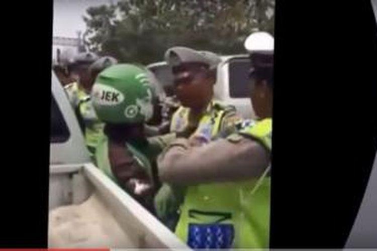 Video yang beredar di youtube memperlihatkan seorang pengemudi go-jek yang dipukul polisi