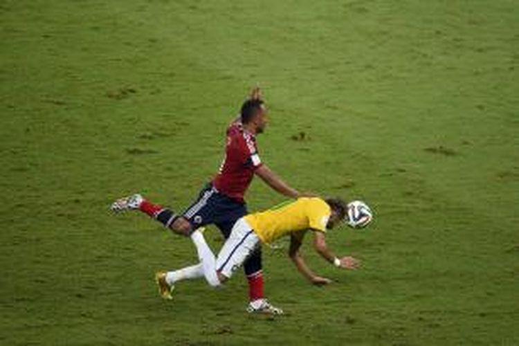 Penyerang Brasil Neymar (berbaju kuning) berbenturan dengan bek Kolombia, Juan Camilo Zuniga, pada laga perempat final Piala Dunia, di Estadio Castelao, Fortaleza, Jumat (4/7/2014).