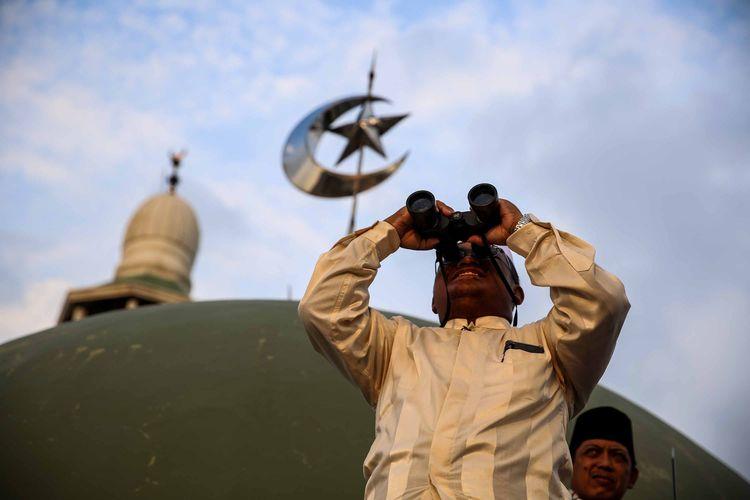 Petugas lembaga Falakiyah pondok pesantren Al-Hidayah Basmol, Jakarta Barat melakukan pemantauan hilal di atas masjid Al-Musariin, Minggu (5/5/2019).