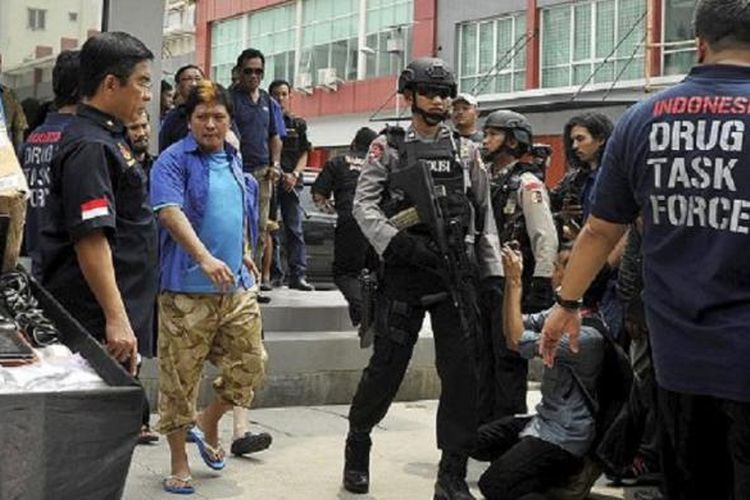Terpidana mati kasus narkoba yang ditahan di Nusakambangan, Freddy Budiman (baju dan kaus biru), dihadirkan dalam rilis pengungkapan pabrik narkoba oleh Direktorat Tindak Pidana Narkoba Polri di ruko Mutiara Taman Palem, Cengkareng, Jakarta Barat, Selasa (14/4). Pabrik narkoba yang memproduksi ekstasi tersebut merupakan jaringan pengedar narkoba yang diduga dikendalikan oleh terpidana mati Freddy Budiman. Jaringan tersebut juga mengedarkan narkoba jenis baru, CC4, yang mempunyai bentuk seperti lembaran prangko.