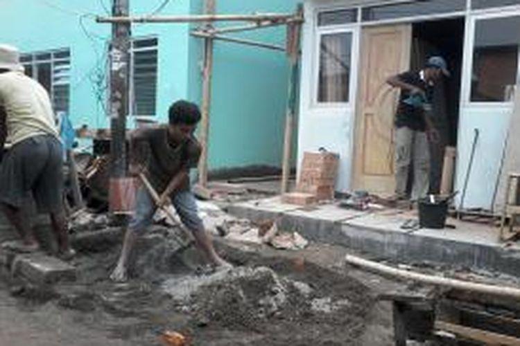 Pekerja bangunan tengah mengerjakan renovasi rumah di RT 14 RW 01, Tanah Tinggi, Johar Baru, Jakarta Pusat, Senin (15/7/2013). Dibantu warga, mereka mempercepat pekerjaan sehingga deretan rumah cantik bisa ditempati sebelum Lebaran.