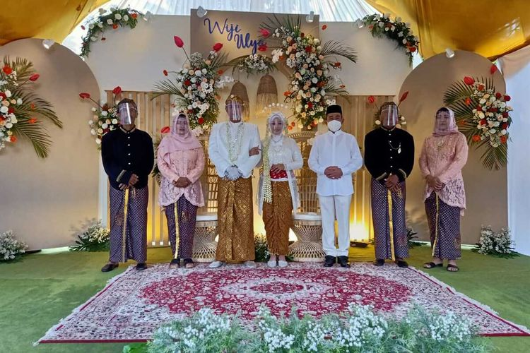Foto sesi pertama saat Haryanto mengenakan maskerberdiri berdampingan dengan sepasang pengantin di Kecamatan Batangan, Kabupaten Pati, Jawa Tengah, Minggu (17/1/2021).