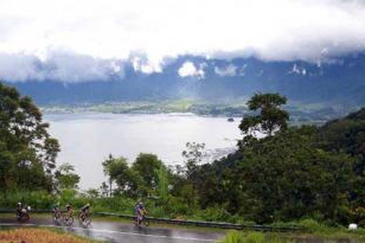 Pebalap sepeda Tour de Singkarak 2013 melintasi kelokan 30 di kawasan obyek wisata Danau Mainjau, Kabupaten Agam, Sumatera Barat, Selasa (4/6/2013).