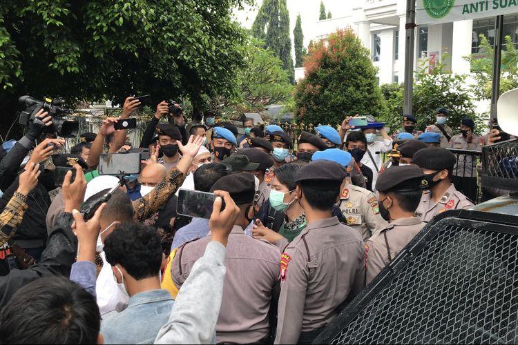 Anggota tim kuasa hukum terdakwa kasus kerumunan dan penghasutan, yaitu Rizieq Shihab, cekcok dengan polisi di depan Pengadilan Negeri Jakarta Timur (PN Jaktim), Cakung, Jakarta Timur pada Selasa (30/3/2021).