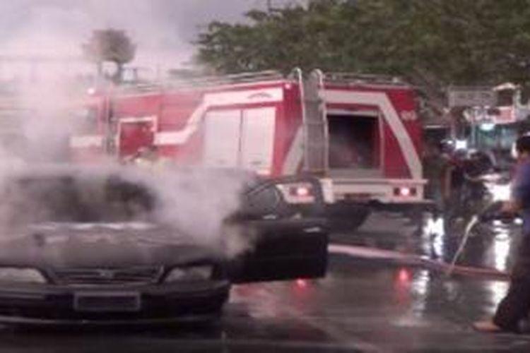 Petugas Pemadam Kebakaran sedang memadamkan api yang membakar mobil sedan milik Syamsudin di Banda Aceh, Jumat (9/5/2014).
