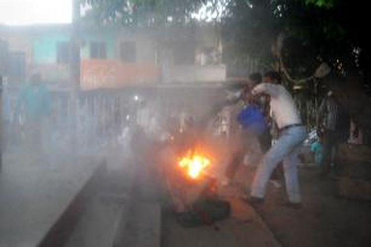 Warga mencoba memadamkan api yang menjilat tubuh seorang pria dan seorang politisi yang tengah menghadiri sebuah rekaman acara debat politik televisi di Sultanpur, India, Senin (28/4/2014).