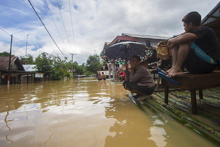 Warga menunggu evakuasi saat  banjir melanda Desa Sungai Raya, Kabupaten Banjar, Kalimantan Selatan. Hujan tiada henti pada Selasa (12/1/2021) berujung petaka dengan meluapnya sungai hampir di seluruh wilayah Kalimantan Selatan, sedikitnya 11 kabupaten/kota porak poranda diterjang banjir termasuk Kota Banjarmasin.