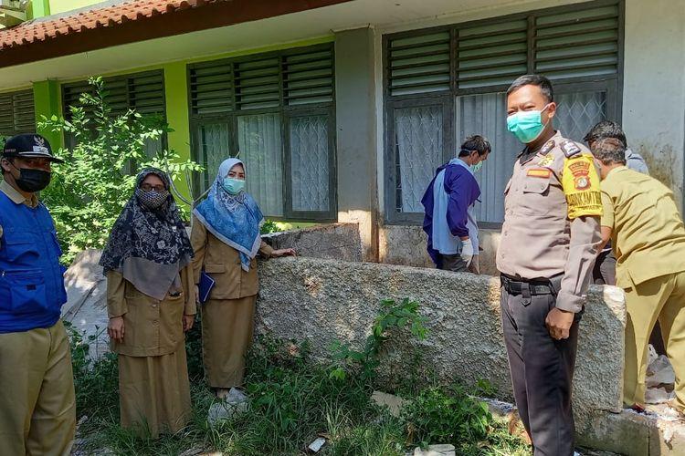 Petugas membersihkan sisa sampah medis berupa ratusan jarum suntik yang tercecer dari vaksinasi Covid-19 massal di SMKN 1 Depok, Tapos, Senin (26/7/2021).