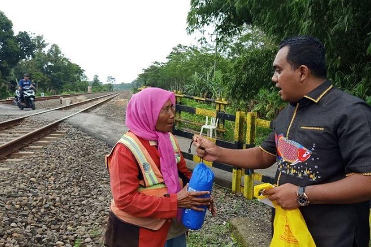Anggota DPRD Kabupaten Pekalongan Jawa Tengah Candra Saputra memberikan bantuan jas hujan dan ponsel ke Kasturah.
