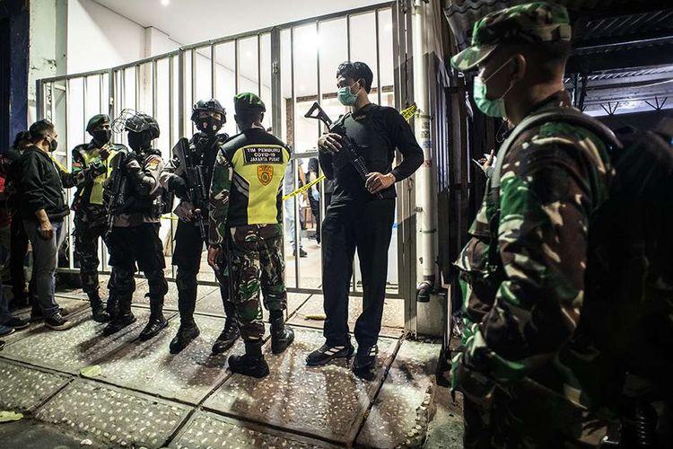 Personel kepolisian bersenjata dan prajurit TNI berjaga saat tim Densus 88 Antiteror melakukan penggeledahan di bekas markas Front Pembela Islam (FPI), Petamburan, Jakarta, Selasa (27/4/2021). Tim Densus 88 Antiteror menggeledah tempat tersebut pascapenangkapan mantan Sekretaris Umum Front Pembela Islam (FPI) Munarman terkait kasus dugaan tidak pidana terorisme.