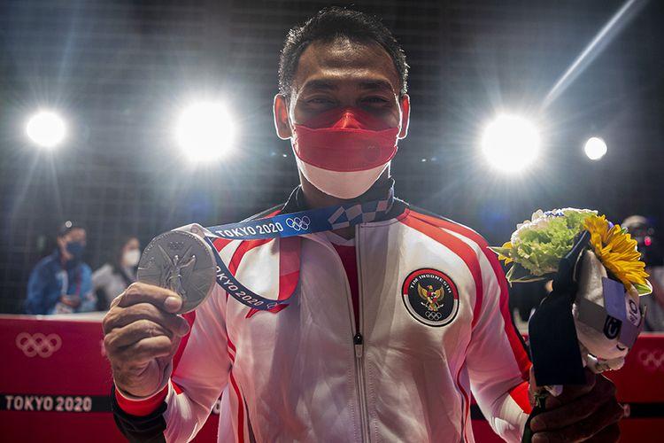 Lifter Indonesia Eko Yuli Irawan menunjukkan medali perak kelas 61 kg putra Grup A Olimpiade Tokyo 2020 di Tokyo International Forum, Tokyo, Jepang, Minggu (25/7/2021). Eko Yuli berhasil mempersembahkan medali perak dengan total angkatan 302 kg.
