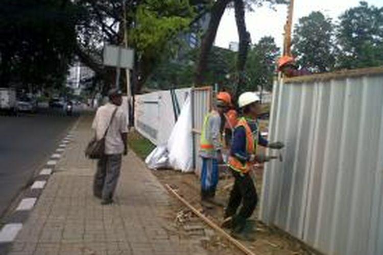 tiga pekerja di MRT di Sudirman -Thamrin  Tiga pekerja terlihat sibuk memasang seng penutup proyek mass rapid transit(MRT) di jalan Thamrin, Jakarta Pusat, Selasa (8/10/2013). Rencananya peletakan batu pertama atau groundbreaking pembangunan konstruksi transportasi berbasis rel atau  mass rapid transit (MRT) akan dilaksanakan pada Kamis mendatang (10/10/2013). Kompas.com/Ummi Hadyah Saleh