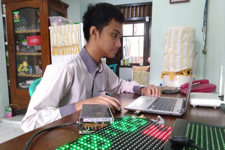 Hanif Arroisi Mukhlis saat melakukan pemrograman untuk jam digital yang diciptakannya bersama sang ayah.