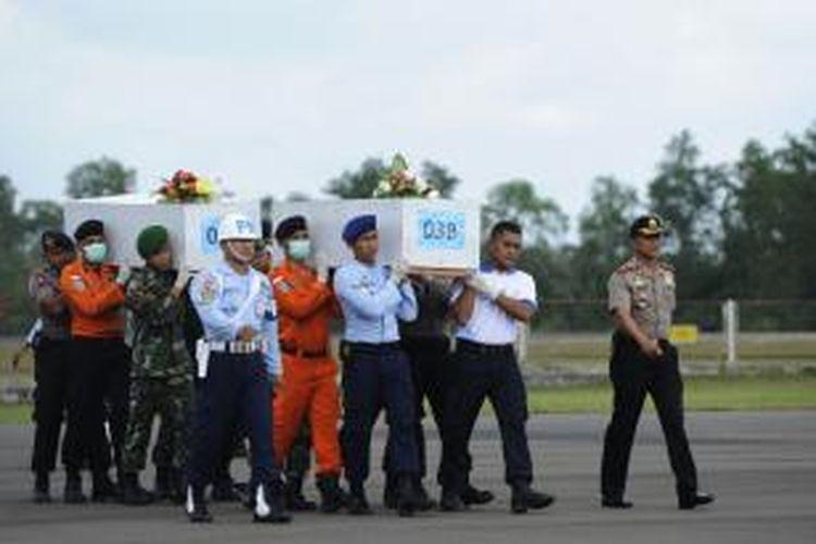 Petugas membawa peti jenazah korban AirAsia QZ 8501 menuju pesawat di Lapangan Udara Iskandar, Pangkalan Bun, Kalimantan Tengah, Rabu (7/1). Sebanyak dua jenazah tersebut akan dibawa ke Surabaya untuk diidentifikasi.