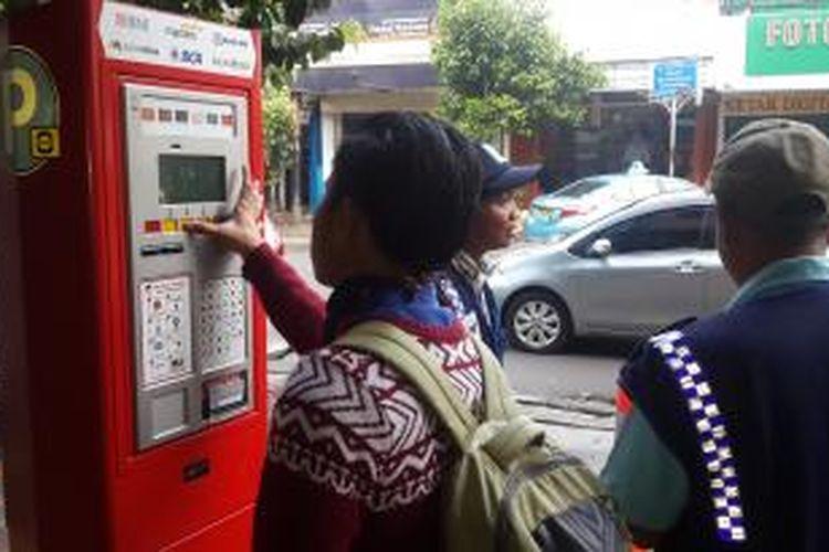 Pengendara saat membayar meteran parkir di Jalan Sabang, Jakarta Pusat, Senin (4/5/2015).