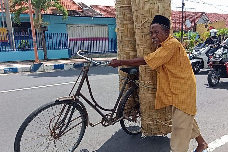 Jumali menuntun julannya di Jalan Jaksa Agung Suprapto, Penganjuran, Kecamatan Banyuwangi, Sabtu (18/9/2021).