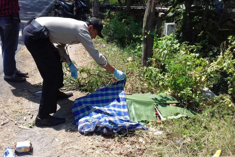 Aparat Polres Ponorogo membuka penutup yang menutupi jenazah korban yang ditemukan tewas di ruas jalan raya Ponorogo - Pacitan di Desa Beton, Kecamatan Siman, Kabupaten Ponorogo, Senin ( 21/8/2017) siang.