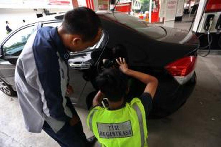 Petugas memasang cincin Radio Frequency Identification (RFID) kepada salah satu mobil mewah di SPBU kawasan Tanah Abang, Jakarta Pusat, Selasa (3/12/2013).