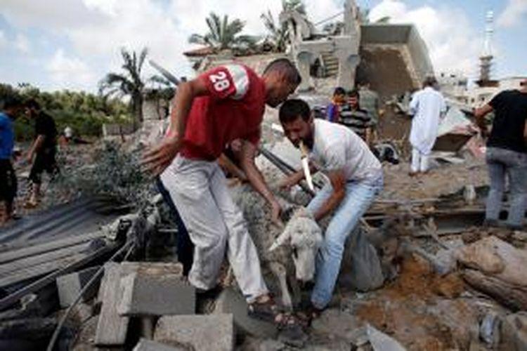Seorang warga Gaza menyelamatkan seekor kambing dari sebuah bangunan yang hancur akibat serangan udara Israel sepanjang Selasa (15/7/2014). Israel kembali melakukan serangkaian serangan ke Jalur Gaza setelah Hamas menolak usulan gencatan senjata yang diajukan Mesir.