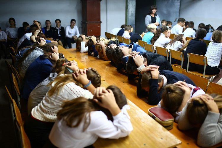 Para siswa Sekolah Nomor 8 di desa Sartana, Ukraina melakukan latihan bagaimana melindungi diri saat terjadi serangan bom.