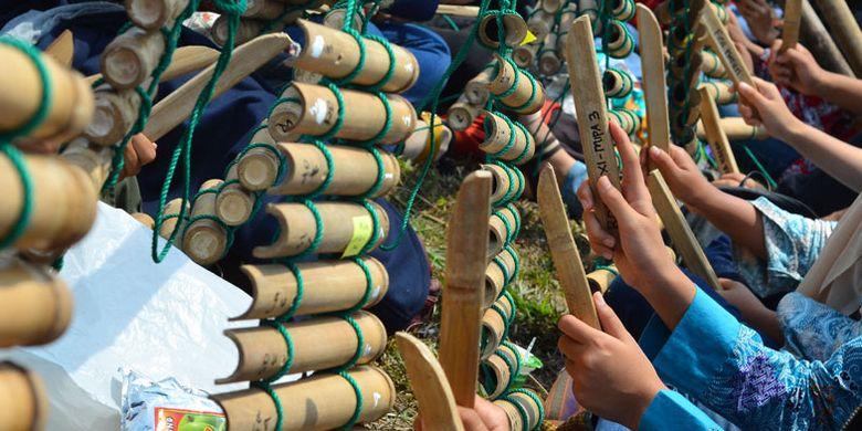 Sejumlah pelajar memainkan alat musik tradisional Calung renteng pada acara Preanger Tourism Fair 2018 di Karangresik, Kota Tasikmalaya, Jawa Barat, Minggu (14/10/2018). Pertunjukan yang dikemas lewat kolaborasi antara calung renteng, angklung, perkusi dan alat musik modern itu dimainkan oleh 1.093 pelajar dari 15 sekolah bertujuan untuk melestarikan calung renteng agar lebih dikenal oleh generasi muda.