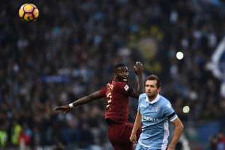 Antonio Rudiger (AS Roma) dan Senad Lulic (Lazio) bentrok dalam perebutan bola pada laga Derbi Roma di Stadion Olimpico, Minggu (4/12/2016).