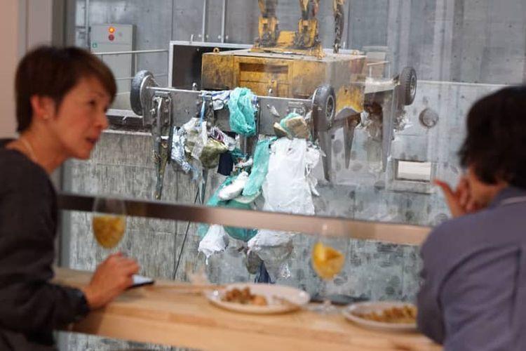 Dua pengunjung tengah menikmati hidangan dengan pemandangan proses pengolahan sampah di depannya.