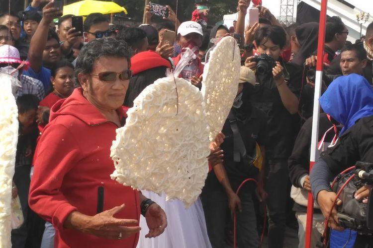 Raja Dangdut Rhoma Irama mengikuti lomba makan kerupuk dalam acara Konser Kemerdekaan Republik Indonesia ke-73, di Partai Carnaval, Ancol, Jakarta Utara, Sabtu (18/8/2018).