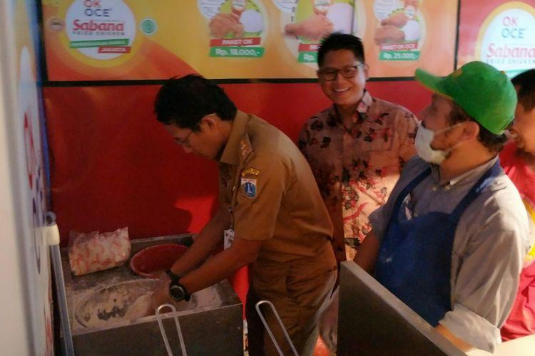 Wakil Gubernur DKI Jakarta Sandiaga Uno mengaduk daging ayam mentah dengan adonan tepung saat berperan sebagai pedagang ayam goreng tepung saat meresmikan kios UMKM di Kantor Kecamatan Tanah Abang, Jakarta Pusat, Selasa (19/12/2017) pagi.