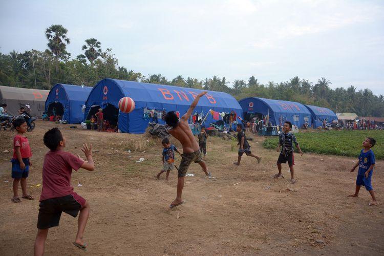 Sejumlah anak pengungsi letusan Gunung Agung bermain bola di posko pengungsian Desa Les, Kabupaten Buleleng, Bali, Minggu (24/9). Jumlah pengungsi Gunung Agung, Kabupaten Karangasem, 2.423 jiwa yang tersebar di 10 titik di Kabupaten Buleleng dan jumlah tersebut terus bertambah karena masih ada beberapa warga yang bertahan di rumahnya walaupun status gunung sudah pada level awas. ANTARA FOTO/Wira Suryantala/ama/17.