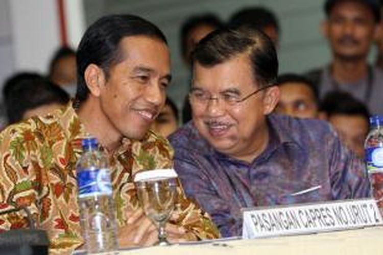 Calon Presiden Joko Widodo berbincang dengan  calon Walkil Presiden Jusuf Kalla saat mendengarkan rekapitulasi hasil perhitungan suara di Kantor Komisi Pemilihan Umum, Jakarta, Selasa (22/7/2014). Pasangan Jokowi-JK akhirnya memenangkan Pilpres 2014 dengan persentase 53,15 persen, mengungguli pasangan Prabowo-Hatta dengan perolehan suara sebanyak 46,85 persen.