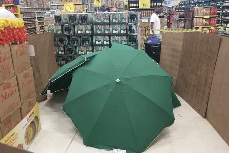 Foto jenazah pegawai supermarket Carrefour Brasil yang meninggal karena serangan jantung, hanya ditutupi kardus dan payung hijau besar, sedangkan toko tetap buka.