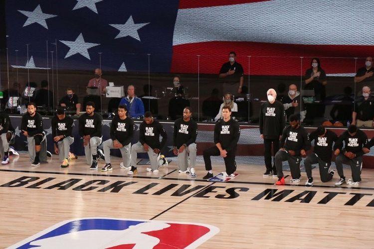 Para pemain San Antonio Spurs dan Sacramento Kings berlutut di sebelah logo Black Lives Matter jelang lanjutan laga NBA di Florida, Amerika Serikat, pada 31 Juli 2020.