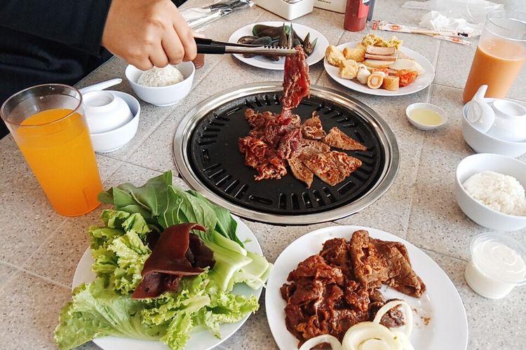 Membakar daging di atas panggangan arang di Hodai AYCE, Kota Malang. Restoran all you can eat di Kota Malang ini baru buka Juni 2020, gerai kedua Desember 2020.