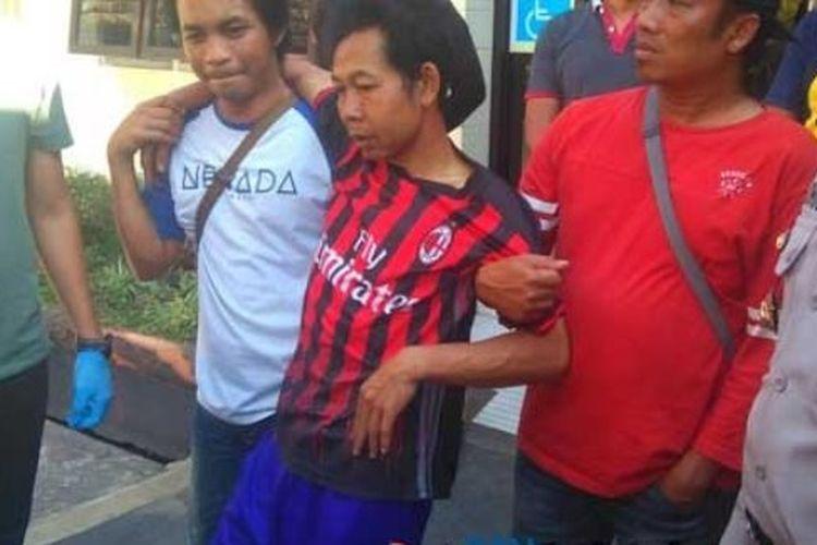 Sobirin (tengah pakai baju klub bola) pelaku penculikan muridnya sendiri saat digiring ke Polres Malang, Sabtu (22/9/2018).