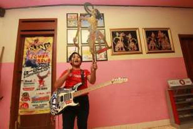 LATIHAN-- Prabu Dylan Jacobuwono Nugroho, siswa kelas VI SD multitalenta sementara latihan kolaborasi wayang dan musik heavy metal di kediamannya di Kota Madiun, Jawa Timur.