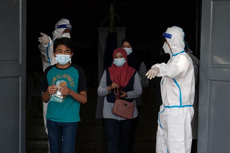 Petugas medis mengenakan APD mempersilakan orang-orang masuk untuk menjalani tes Covid-19 di Shah Alam, pinggiran Kuala Lumpur, Malaysia, pada 17 Februari 2021.