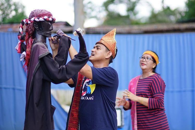 Para wisatawan menari bersama dengan boneka Sigale-gale di Samosir, Sumatera Utara.