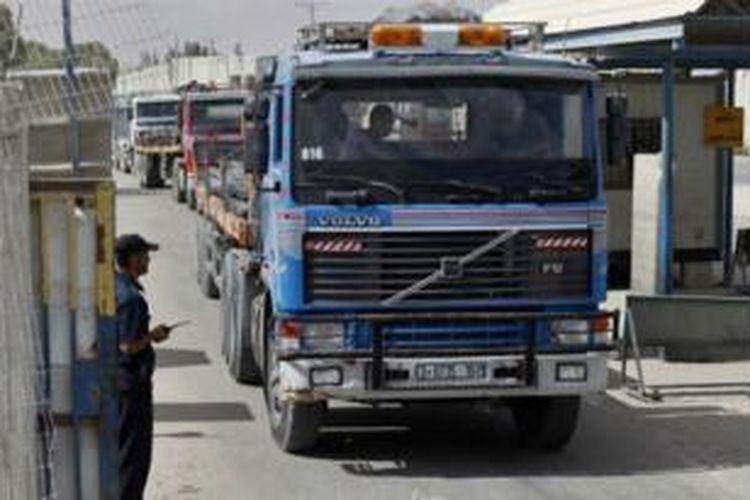 Polisi mengawasi truk yang membawa besi masuk ke Gaza melalui perbatasan Kerem Shalom.