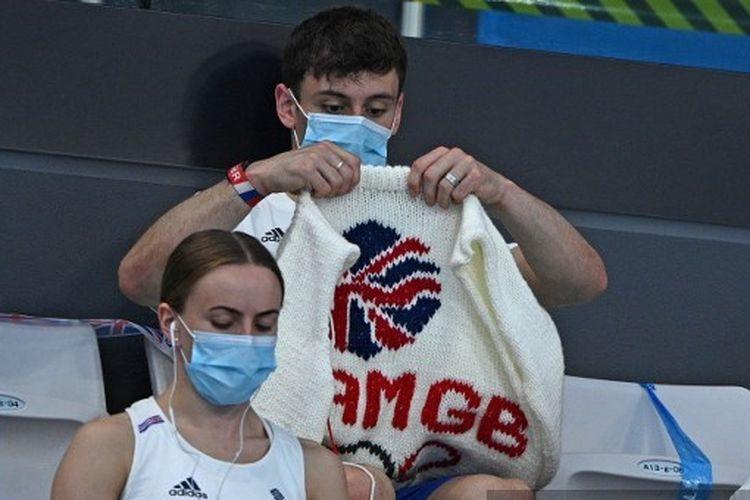 Tom Daley tengah merajut saat menyaksikan babak penyisihan loncat indah nomor 3 meter putra di Olimpiade Tokyo, Senin (2/8/2021).